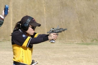 A young female shooter using a heavily modified 1911 in a contemporary shooting competition.